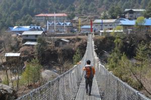 Kaji Sherpa, veteran guide, on a long swinging bridge leading to the village of Phakding