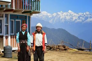 Innkeepers of Nagthali Pass posing in front of their welcoming lodge and the mountains of Langtang