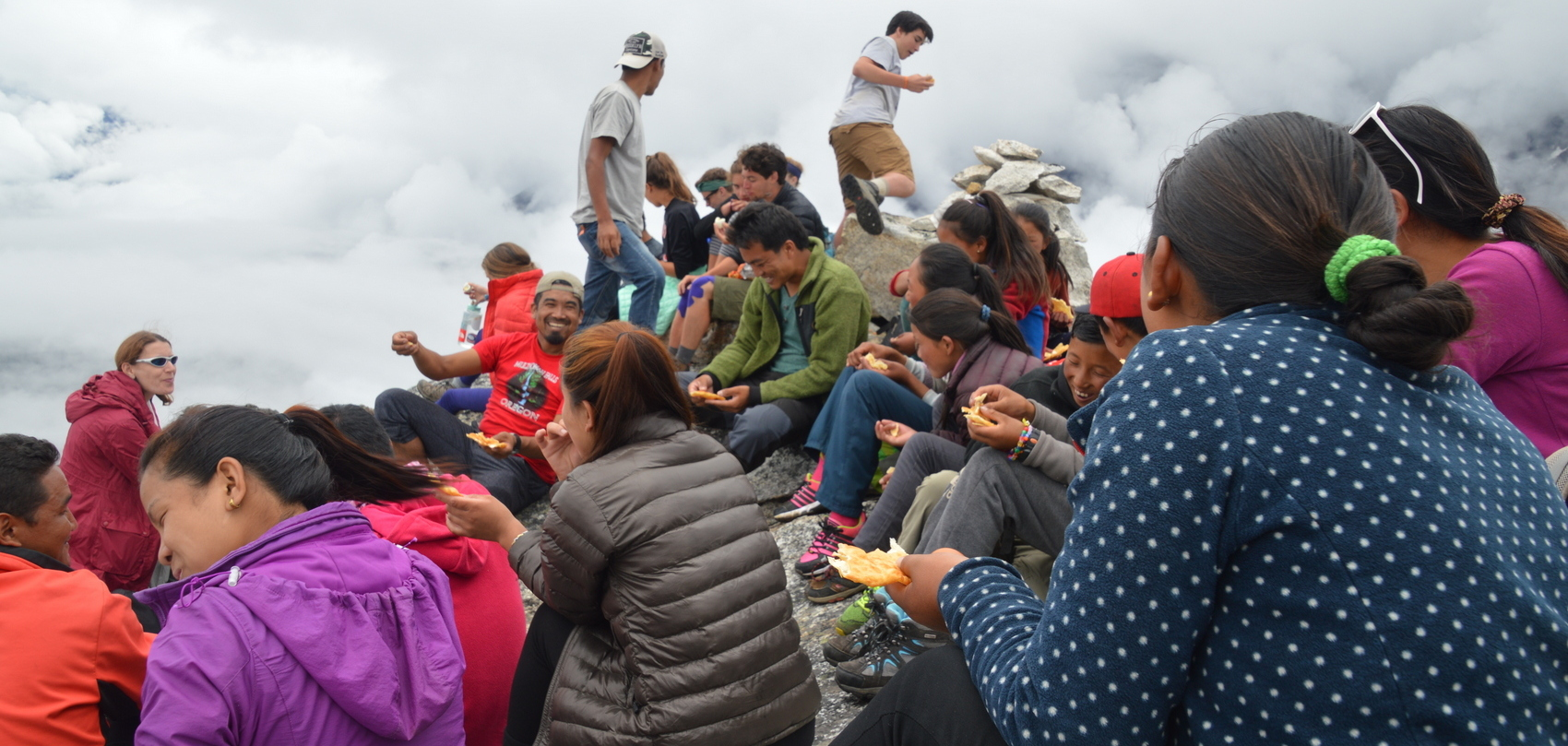 Students and Sherpas eating a packed lunch at the trekkers' summit of Sumdur Peak