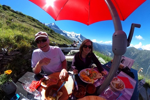 Two people having lunch under a red umbrella on the slopes of Aiguille du Midi, above Chamonix, France