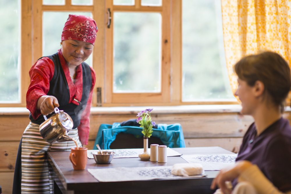 Sherpani serving tea to a guest in an Everest lodge