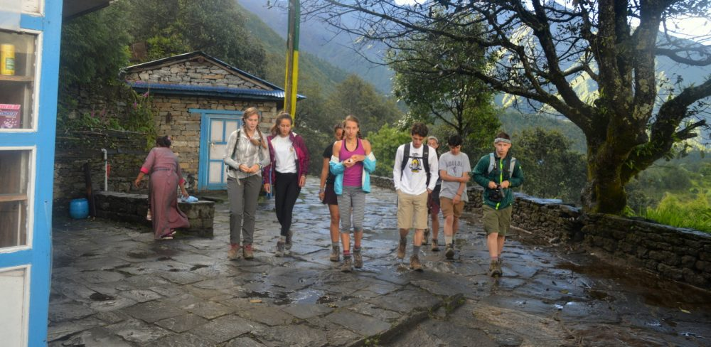 A group of students begins their trekking day on a wet morning in Chaurikharka, Nepal