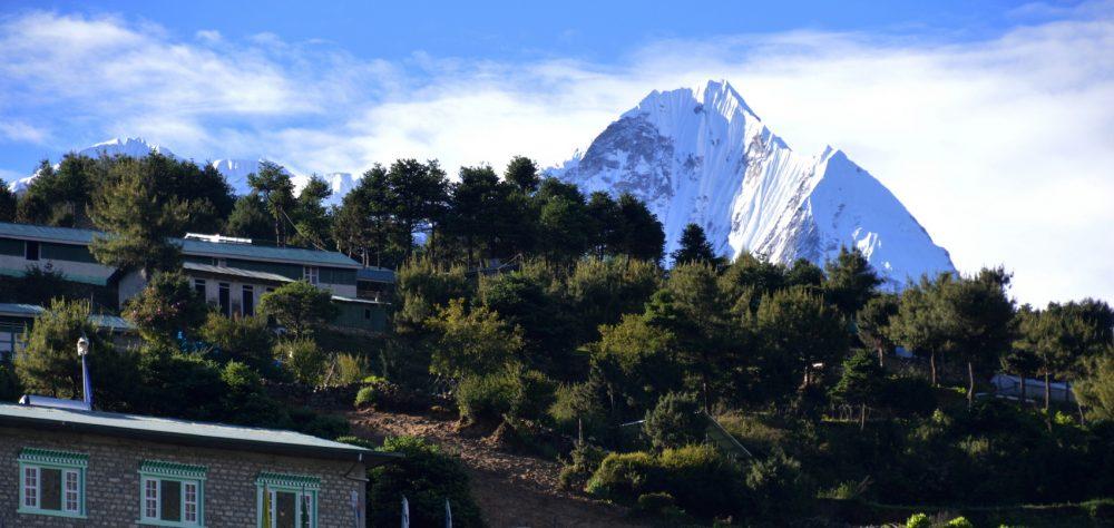A snowy Himalayan peak, Kusum Kanguru, rises above the Sherpa town of Namche Bazaar