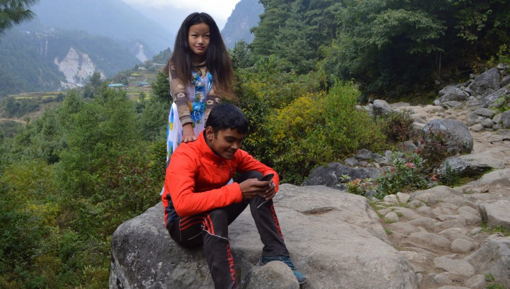 A girl in a princess dress and a boy in a track suit pose for a photo along the Everest trail