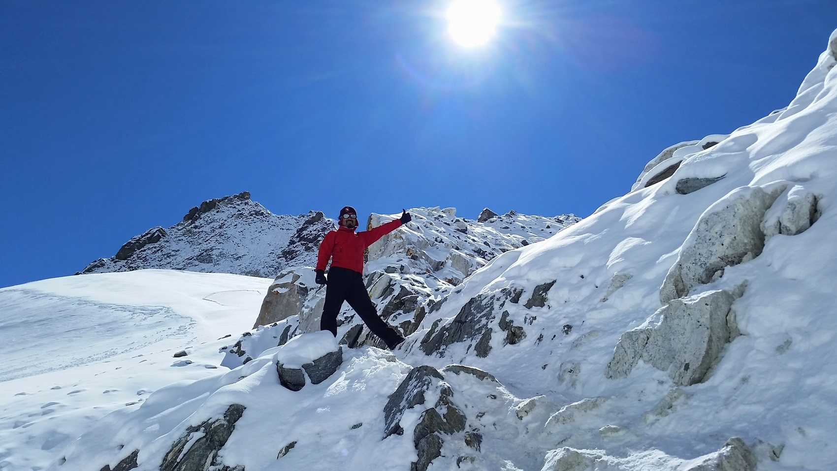 A Sherpa on snowy Cho La Pass gives the thumbs up signal under sunny, blue skies