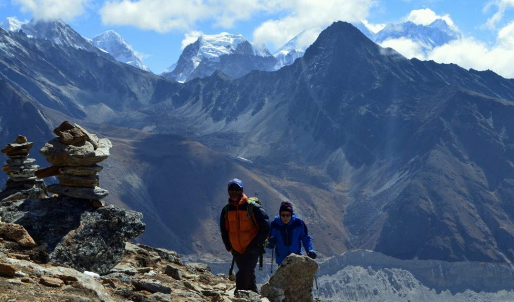 Two hikers climbing Gokyo Ri with a black mountain and Mt Everest visible behind
