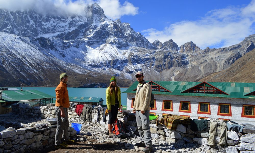 Three trekkers doing laundry above the turquoise lakes of Gokyo