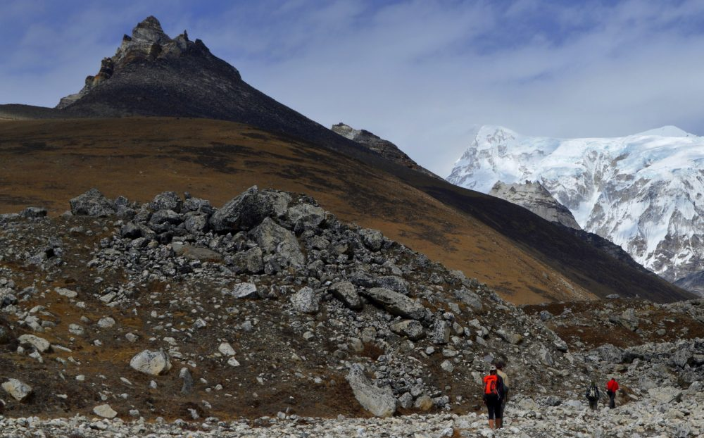 A spire of a mountain rises above the 4th Lake in the Gokyo Valley with the glaciated peaks around Cho Oyu on the right