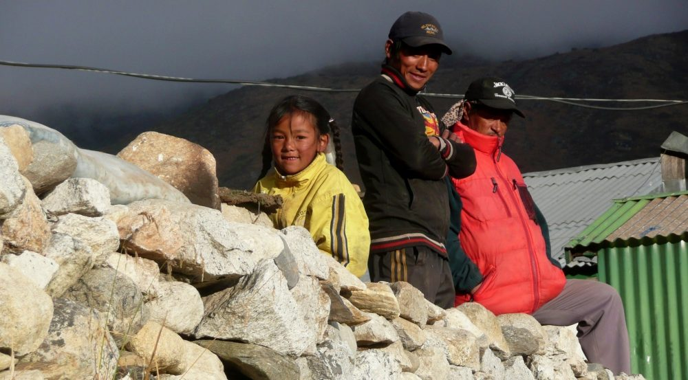 In the Everest village of Pangboche, a young girl sits on a wall with two trekking guides