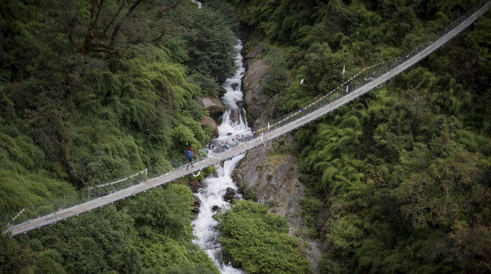 A backpacker walks over a long swinging bridge above a waterfall and jungle foliage