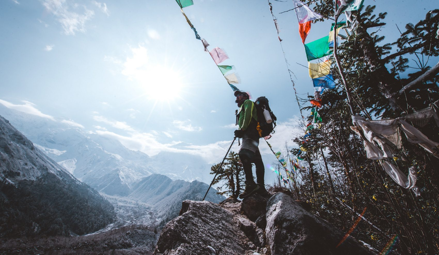 A Sherpa stands on an overlook underneath prayer flags on the Manaslu Circuit