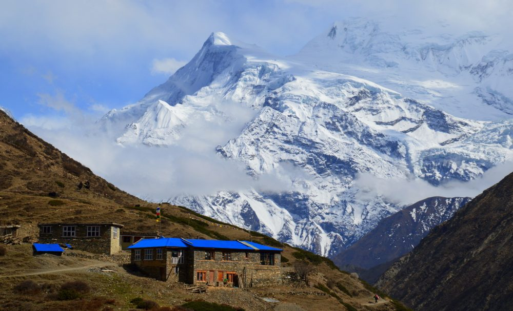 A new lodge with a blue roof is being built underneath snowy mountains of the Annapurnas