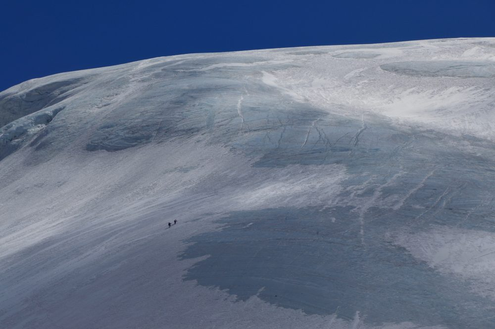 Two Sherpas climbing blue ice on a high mountain in the Annapurnas on a clear day