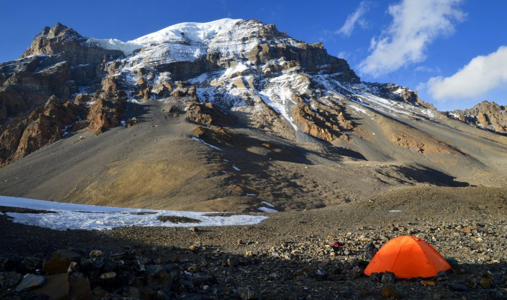 An orange tent is set up on top of the Thorong La with glaciated mountains above