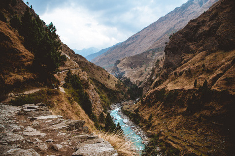 Blue glacial waters accentuate brown grass below a rugged trail in the Manaslu Himalaya