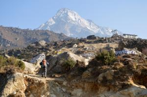 Kaji Sherpa on the trail to Thame w/ the sacred, and unclimbed, Khumbi La mountain looming 7,000 ft above