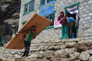 In the mountains of Nepal, everything is carried with a strap over the head, from 100 lb. loads of plywood to this baby in the basket