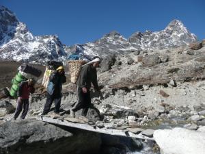 Porters crossing a flimsy bridge after crossing Cho La