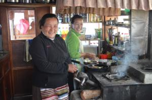 Mother and daughter cooking for guests near Lukla