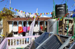Rooftop jungle of solar panels, prayer flags and Himal in Thulo Syabru