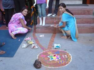 These shopkeepers create intricate art on the sidewalk for Laxmi puja . . . Laxmi is the goddess of wealth, so they're showing her the way to their shops with the adorned mud path
